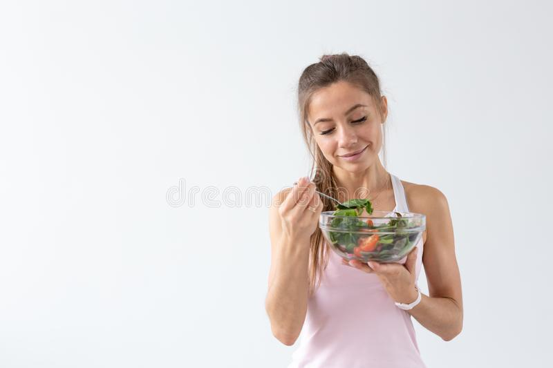 People, food and diet concept - Portrait of woman eating healthy food over white background with copy space.  royalty free stock images