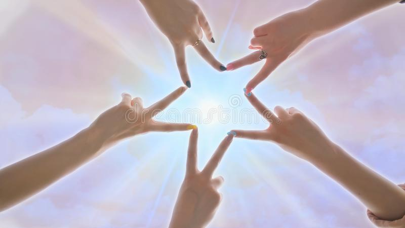 People forming star shape with their fingers against the backdrop of a pink magical sky with shining rays of the sun. People forming star shape with their royalty free stock image