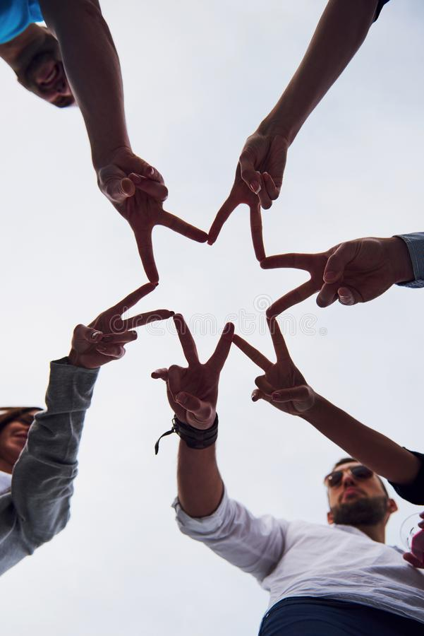 People forming star shape with their fingers.  royalty free stock photo