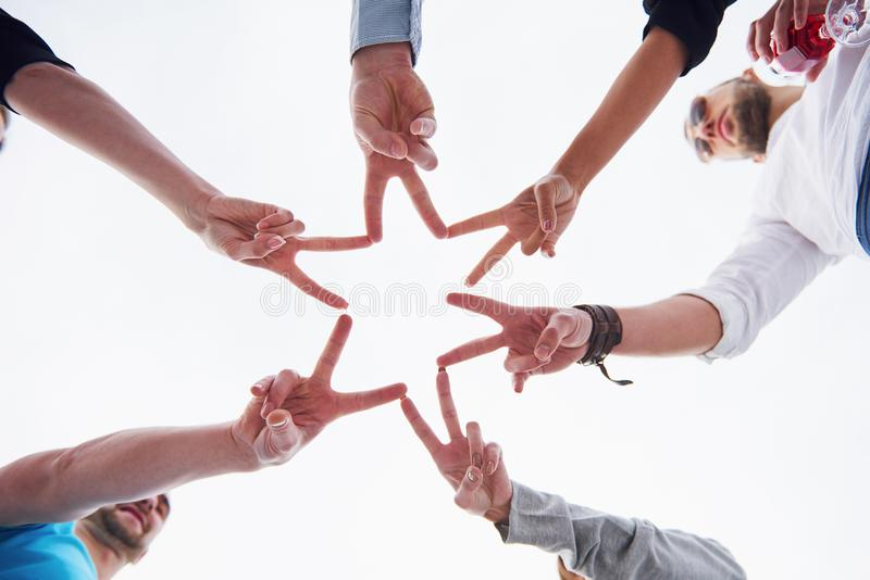 People forming star shape with their fingers.  stock image