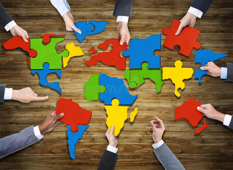 People Forming World Map with Puzzle Pieces. Aerial View of People Forming World Map with Puzzle Pieces royalty free stock photo