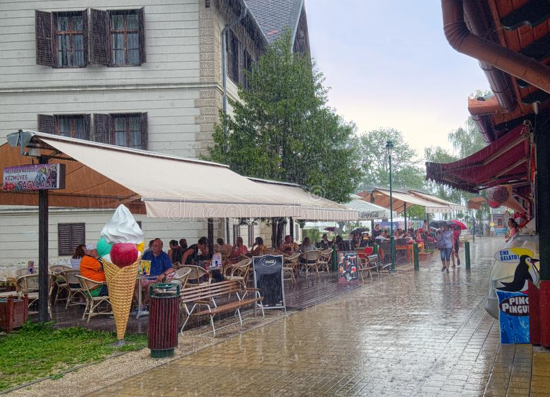 Summer rain in Keszthely town, Hungary. People found a shelter inside of an outdoor cafe while heavy rain is falling in Hungarian town of Keszthely circa June