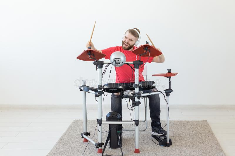People, free time and hobby concept - Cool male drummer over white room background stock photo