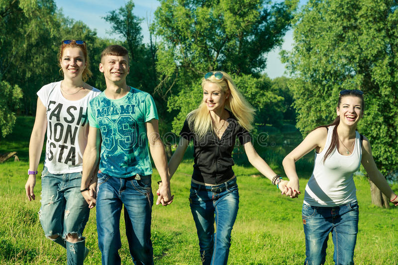 People, freedom, happiness, and teenage concept - group of happy friends go out and fun on a background of green trees royalty free stock photography