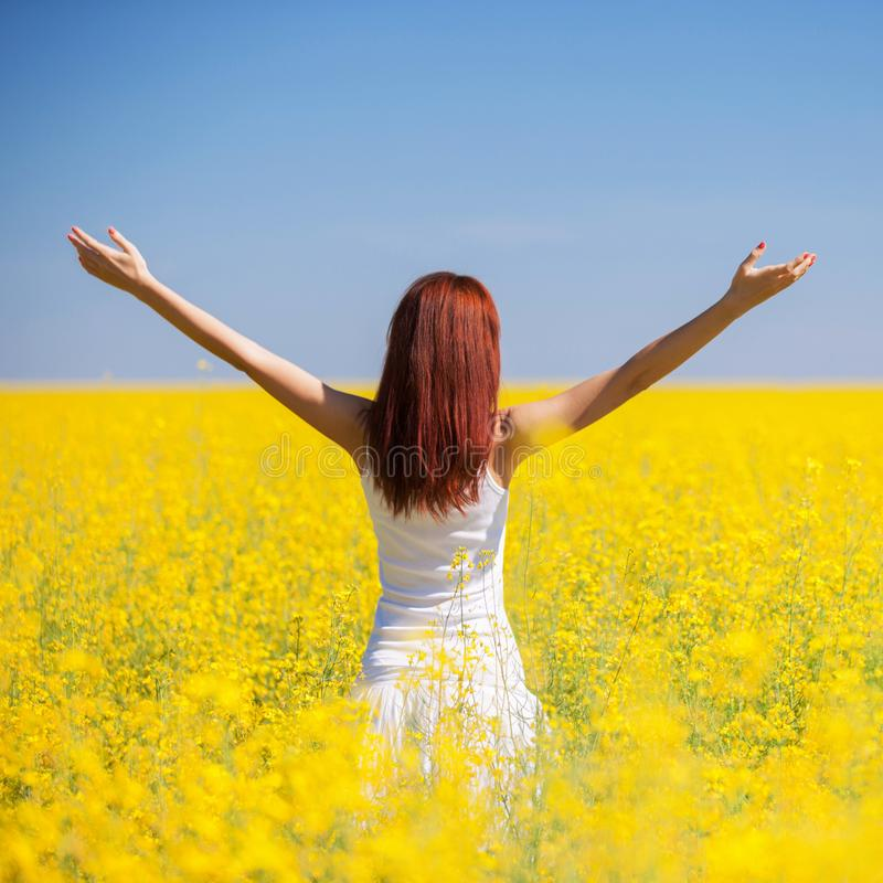 People freedom success concept. Happy woman in the field with flowers at sunny day in the countryside. Nature beauty background, stock photo