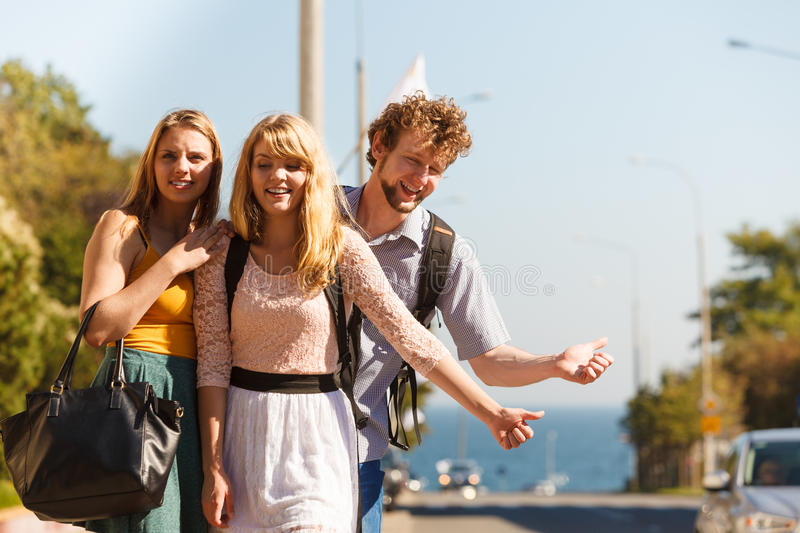 People friends hitchhiking on summer vacation. Young people friends hitchhiking on summer vacation. Happy women and men tourists beside road with thumb up stock photos