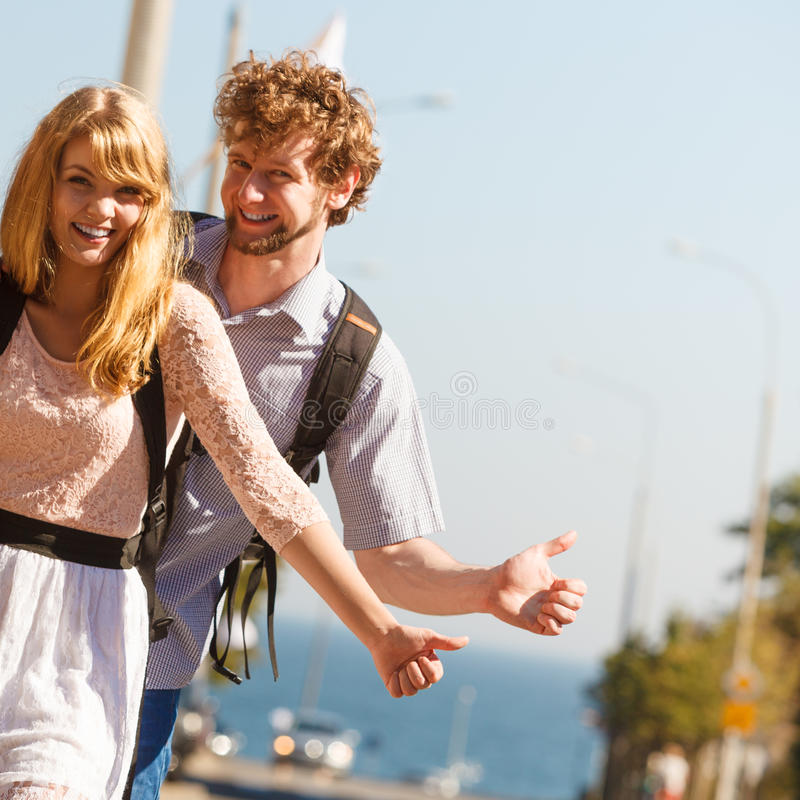 People friends hitchhiking on summer vacation. Young people friends hitchhiking on summer vacation. Happy women and men tourists beside road with thumb up royalty free stock image