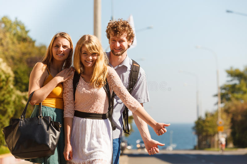 People friends hitchhiking on summer vacation. Young people friends hitchhiking on summer vacation. Happy women and men tourists beside road with thumb up royalty free stock photo