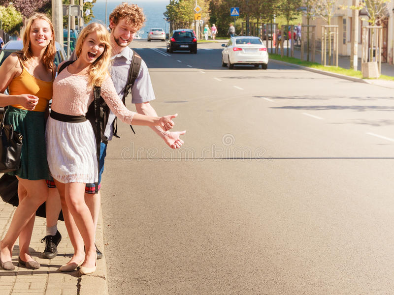 People friends hitchhiking on summer vacation. Young people friends hitchhiking on summer vacation. Happy women and men tourists beside road with thumb up stock image