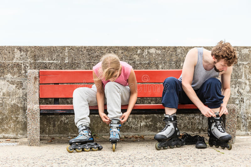 People friends putting on roller skates outdoor. stock photos