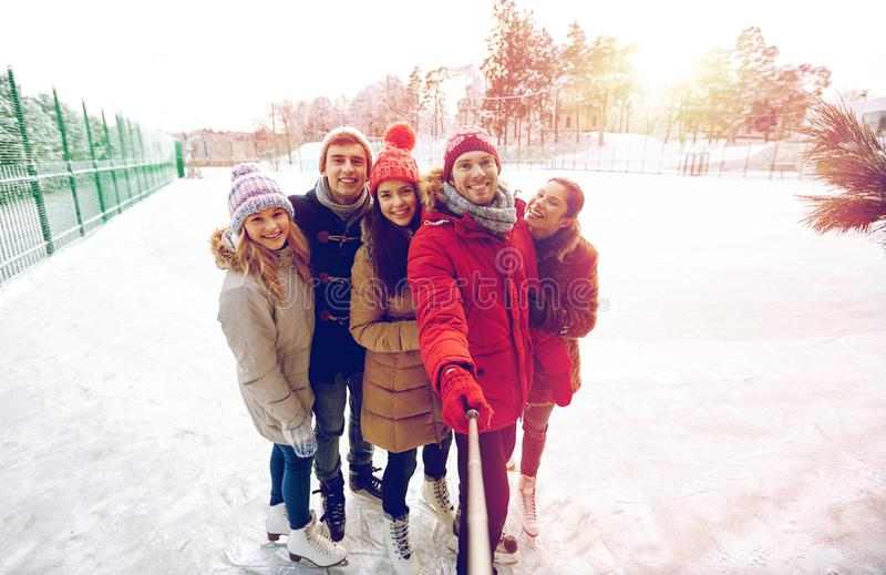 Happy friends with smartphone on ice skating rink stock photo