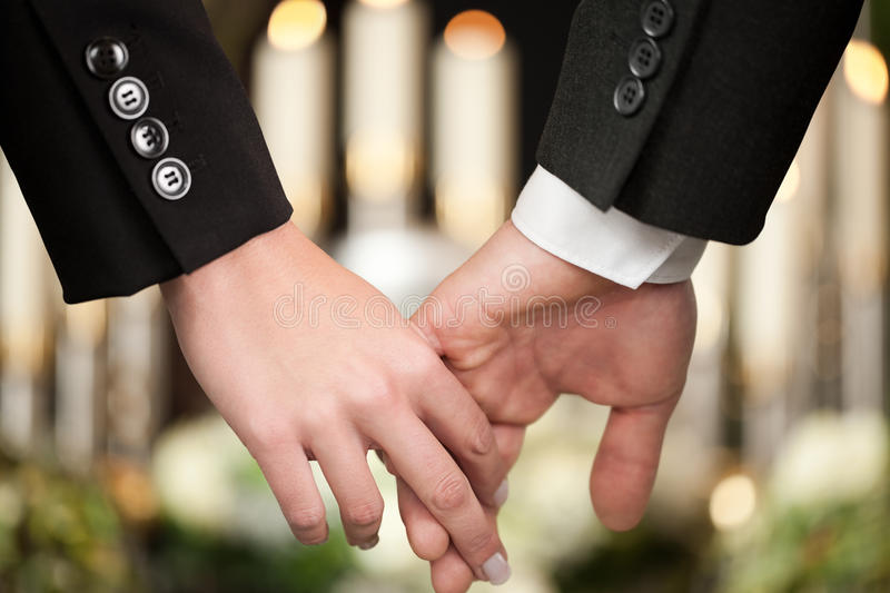 People at funeral consoling each other. Religion, death and dolor - couple at funeral holding hands consoling each other in view of the loss royalty free stock images