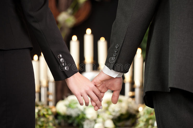 People at funeral consoling each other. Religion, death and dolor - couple at funeral holding hands consoling each other in view of the loss stock photography