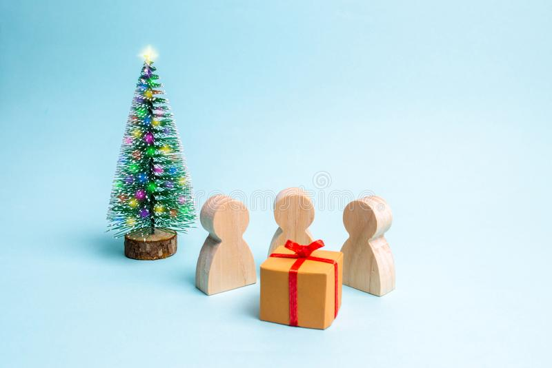 People gathered around the gift and are ready to open it. Family holiday, Christmas and New Year. Sale of gifts. Sell-out. stock photo