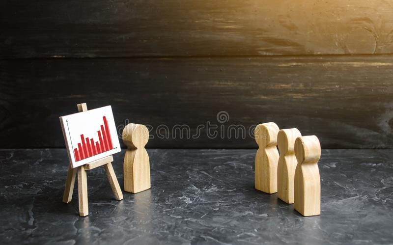 People gathered for a meeting and look at the speech of the leader. Profit and income analysis, briefing and business webinar. stock photography