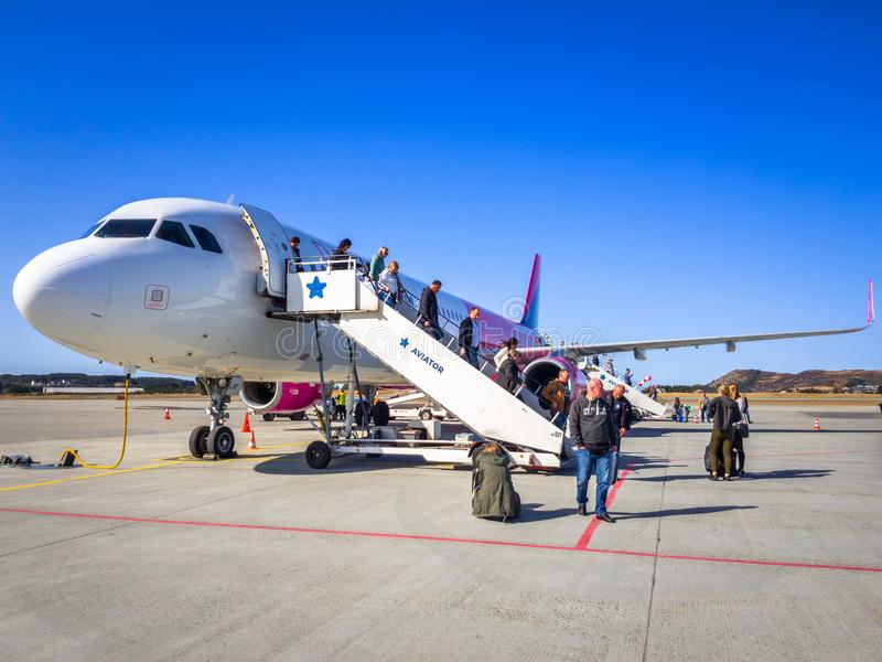 People getting off Wizz air plane. Alesund, Norway - April 13, 2018: People getting off Wizz air plane on Alesund Vigra Airport in Norway. Wizz air is a low-cost royalty free stock image