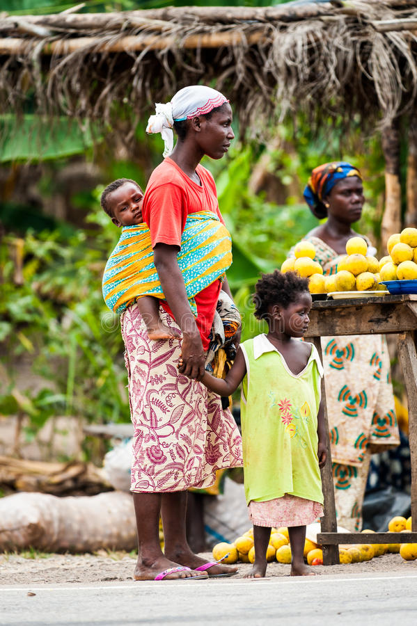 People in GHANA. ACCRA, GHANA - MARCH 2, 2012: Unidentified Ghanaian woman with her child on her back at the market in the street in Ghana. People of Ghana royalty free stock image