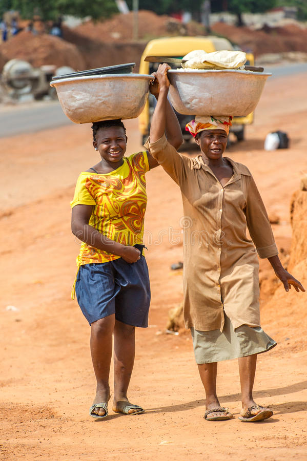 People in GHANA. ACCRA, GHANA - MARCH 6, 2012: Unidentified Ghanaian women carry buckets on their heads in the street in Ghana. People of Ghana suffer of poverty royalty free stock photography