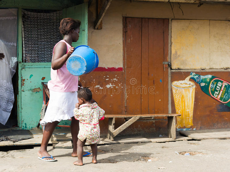 People in GHANA. ACCRA, GHANA - MARCH 2, 2012: Unidentified woman anf her little daughter in the street in Ghana. People of Ghana suffer of poverty due to the stock photo