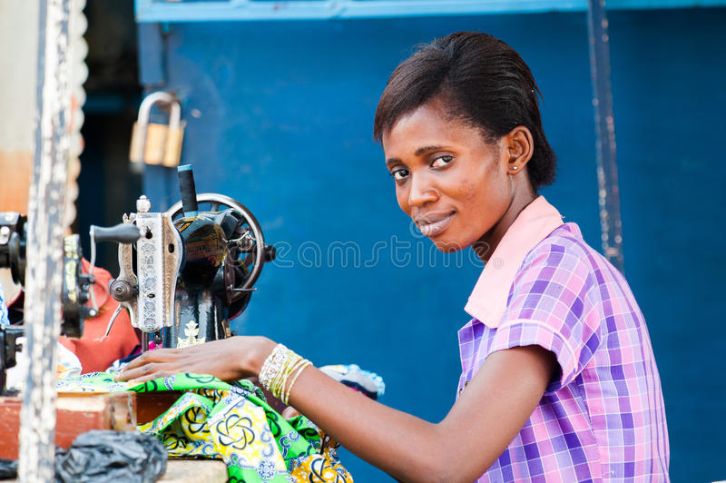 People in GHANA. GHANA - MARCH 2, 2012: Unindentified Ghanaian woman works with a sewing machine in Ghana, on March 2nd, 2012. People in Ghana suffer from stock photo