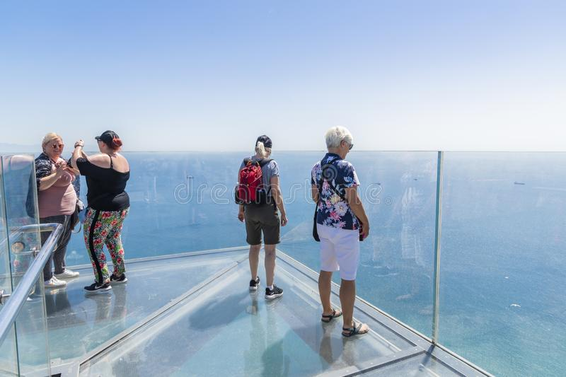 People at Gibraltar Skywalk standing on glass platform. Viewing the Mediterranean sea.  Gibraltar, Europe. Scary and breathtaking experience royalty free stock photography