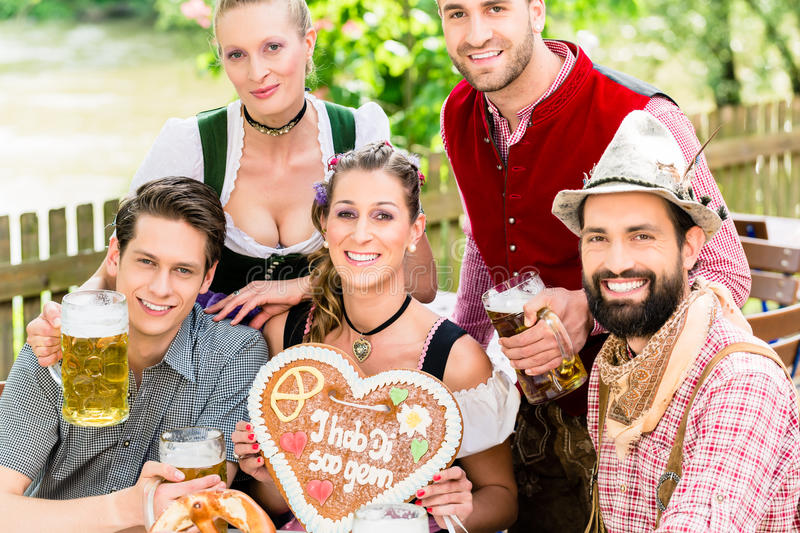 People with gingerbread heart in beer garden royalty free stock photos