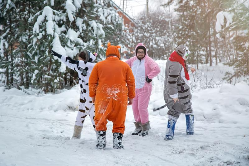 4 people, 2 girls and 2 mens with beard in kigurumi in snow winter forest. Pajama costume pig cow kangaroo and cat. Fun with royalty free stock photography