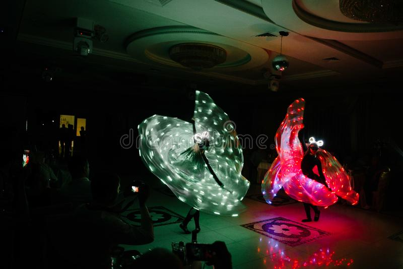 People in glowing costumes dancing in the dark stock images