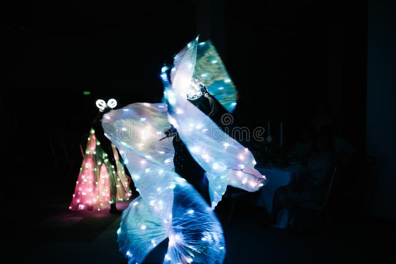 People in glowing costumes dancing in the dark. People in luminous costumes dance in the dark for a holiday, event, dancing, entertainment, dancer, light, glow stock photo