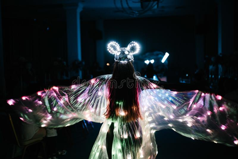 People in glowing costumes dancing in the dark royalty free stock images
