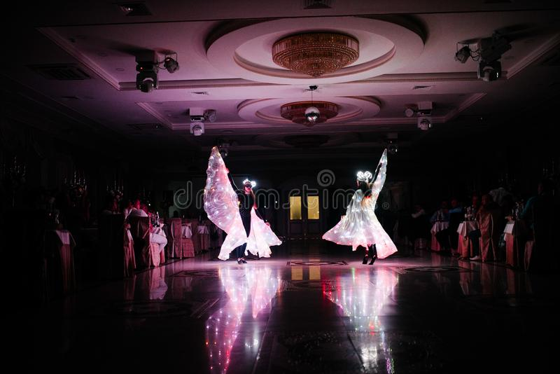People in glowing costumes dancing in the dark. People in luminous costumes dance in the dark for a holiday, event, dancing, entertainment, dancer, light, glow royalty free stock photography