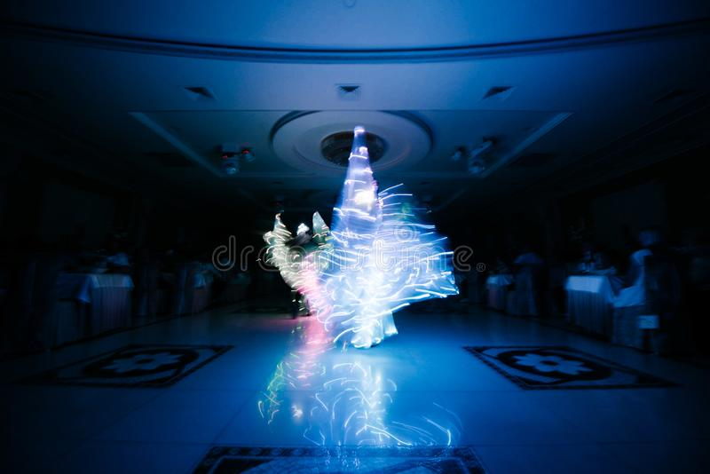 People in glowing costumes dancing in the dark. People in luminous costumes dance in the dark for a holiday, event, dancing, entertainment, dancer, light, glow stock image