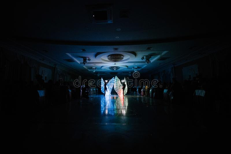 People in glowing costumes dancing in the dark. People in luminous costumes dance in the dark for a holiday, event, dancing, entertainment, dancer, light, glow stock photography