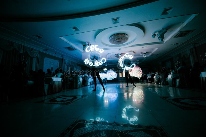People in glowing costumes dancing in the dark. People in luminous costumes dance in the dark for a holiday, event, dancing, entertainment, dancer, light, glow royalty free stock photo