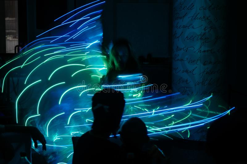 People in glowing costumes dancing in the dark. People in luminous costumes dance in the dark for a holiday, event, dancing, entertainment, dancer, light, glow stock images