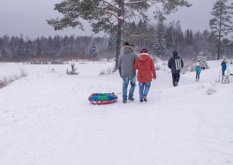 People go with accessories for a winter toboggan run in the snow stock image