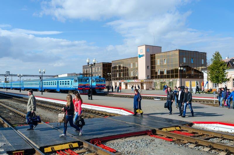 People go to landing platform of railway station in Mogilev, Belarus. MOGILEV, BELARUS - APRIL 25, 2015: Unidentified people go to landing platform of railway stock photo