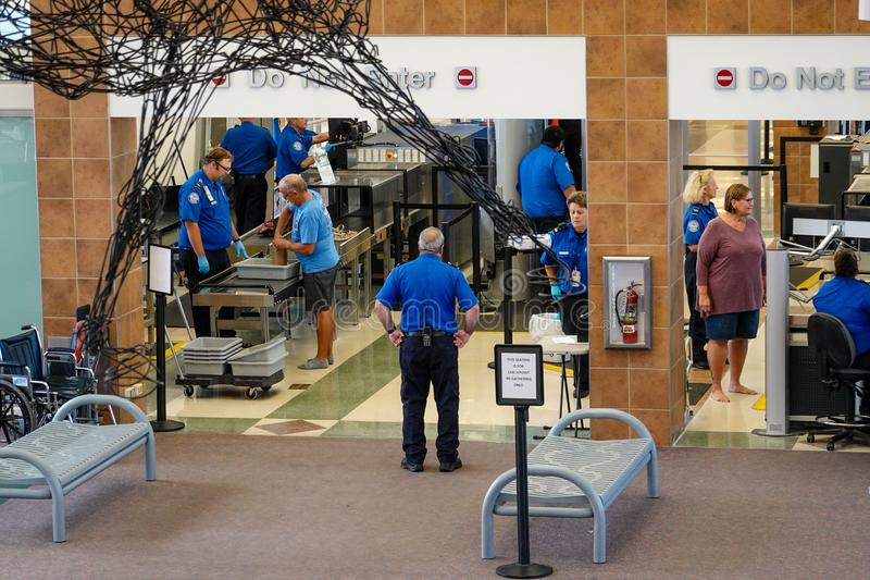 People going through TSA security at a small regional airport. Bloomington,IL/USA-8/25/19: People going through TSA security at a small regional airport stock photo