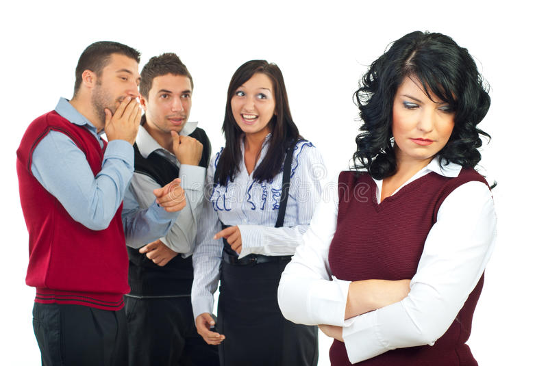 People gossip. Three people gossip and joke in background about their colleague woman and she standing with hands crossed and looking down with a sad face, check stock image