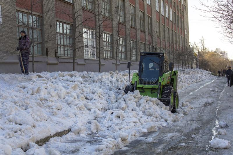 People and green snowblower loader removes snow from the city streets royalty free stock images