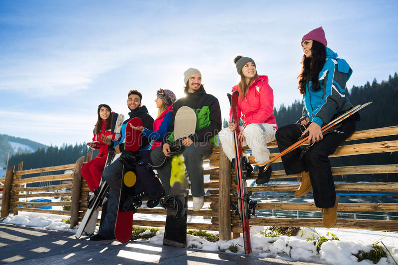 People Group With Snowboard Ski Resort Snow Winter Mountain Cheerful Friends Sitting On Wooden Hence Talking. Extreme Sport Vacation stock photos
