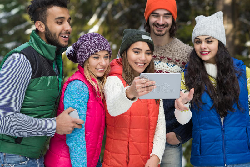 People Group Using Tablet Computer Snow Forest Happy Smiling Young Friends Walking Outdoor Winter. Pine Woods royalty free stock images