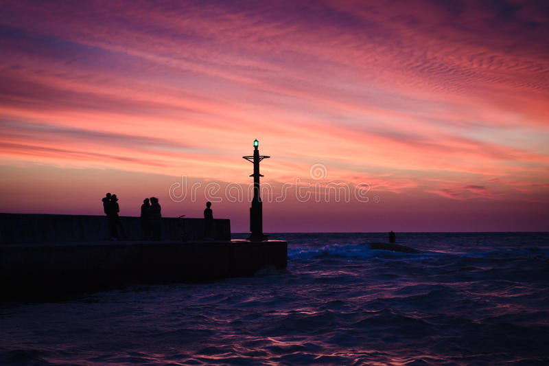 People on groyne with sunset stock images