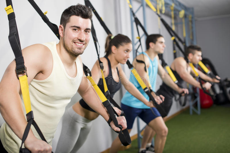 People at gym doing elastic rope exercises stock images