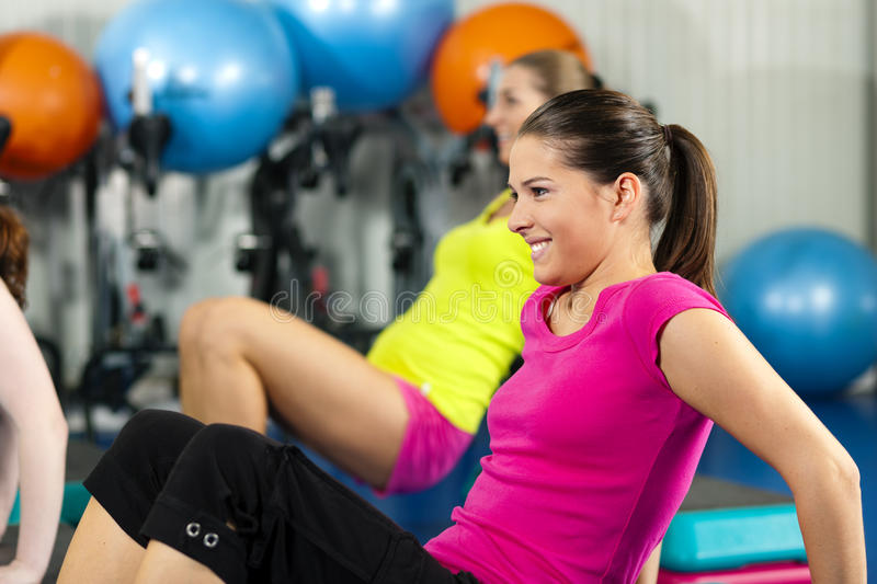 People in gym on step board. Fitness People in gym on step board; strengthening the abdominal muscles stock photo
