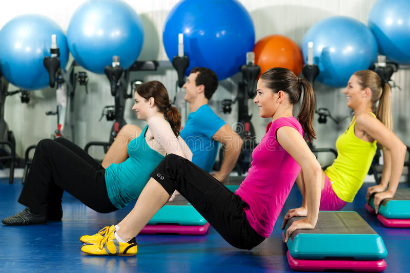 People in gym on step board. Fitness People in gym on step board; strengthening the abdominal muscles stock photos