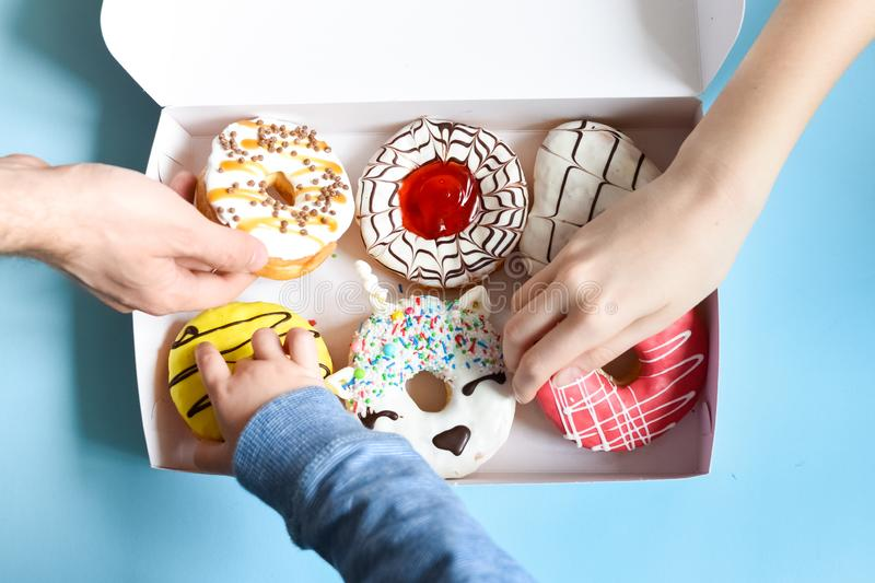 People hands grabbing donuts. People hands takes donuts from donuts box over blue background. Family eating doughnuts from food delivery. Unhealthy lifestyle royalty free stock photography