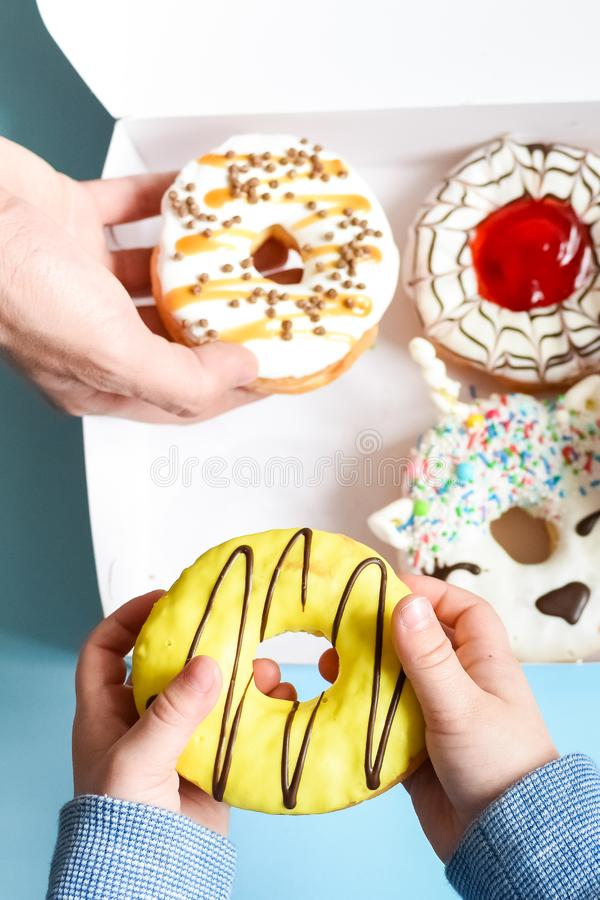 People hands grabbing donuts. People hands takes donuts from donuts box over blue background. Family eating doughnuts from food delivery. Unhealthy lifestyle royalty free stock images