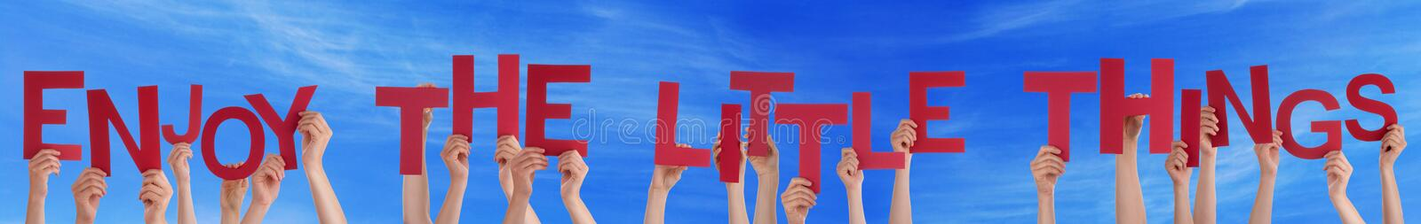 People Hands Holding Word Enjoy The Little Things Blue Sky. Many Caucasian People And Hands Holding Red Letters Or Characters Building The English Word Enjoy The stock photo