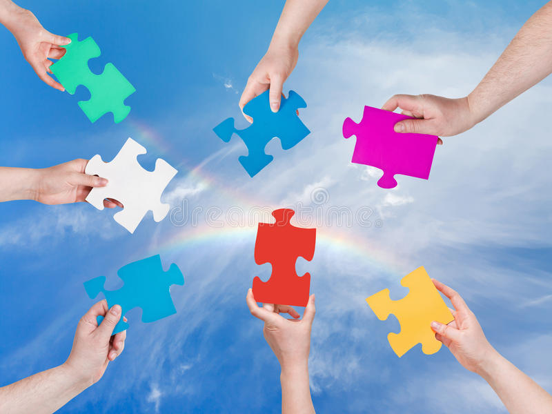 People hands with puzzle pieces with rainbow royalty free stock images